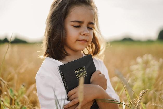 女の子は彼女の手で聖書を保持しています。フィールドで聖書を読む。信仰、霊性、宗教のコンセプト。平和、希望