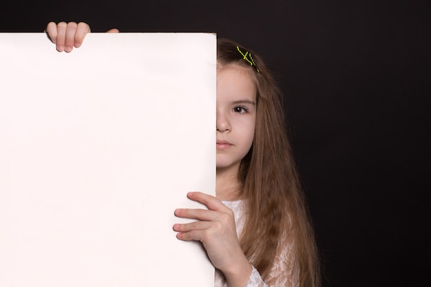 Girl holds a blank space for your advertising