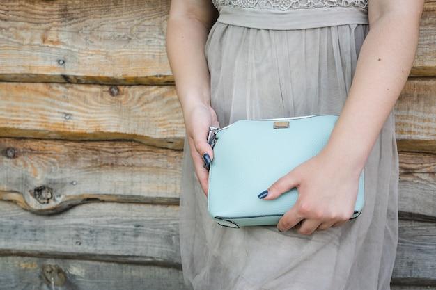 Girl holds blue handbag on wooden background.