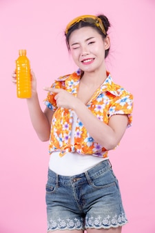 The girl holds a bottle of orange juice on a pink background.
