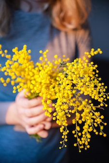 A girl holds a bouquet of spring mimosa flowers in her hands, in the setting sun