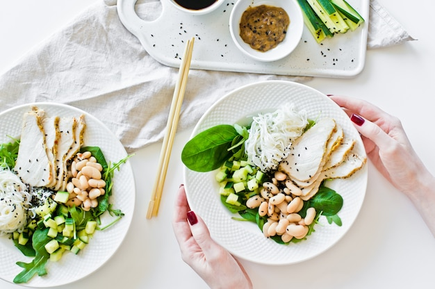 The girl holds a bowl of healthy balanced food, with glass noodles, beans, chicken breast, spinach, arugula and cucumber