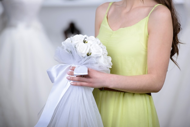 The girl holds a bridal bouquet in the hands of the store.