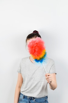 Girl holds brush to clean dust and closes her face on grey wall