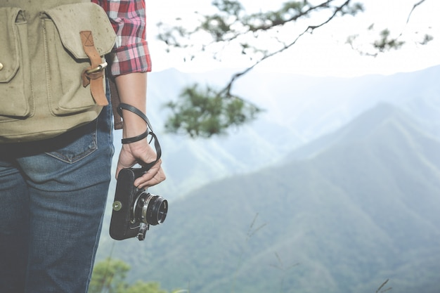 The girl holds a camera, hiking in the tropical forest, along with backpacks in the forest, adventure, travel, tourism, climbingม hike.