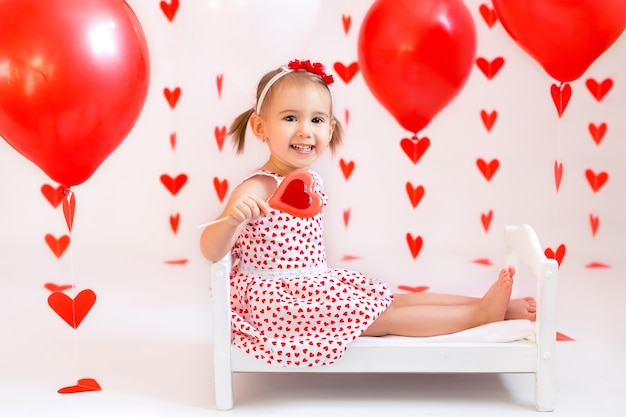 A girl holds a candy on a background of red balls and hearts