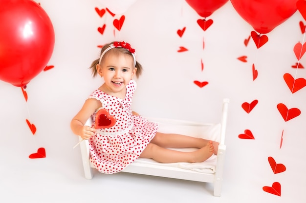A girl holds a candy on a background of red balls and hearts.