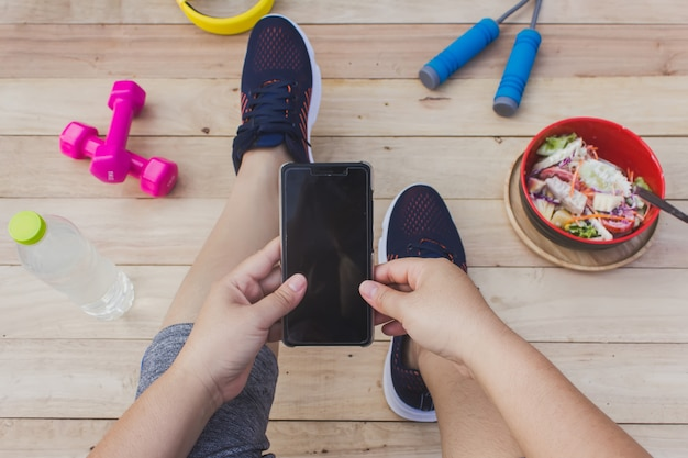 The girl holds a cell phone with exercise equipment, a wooden floor.