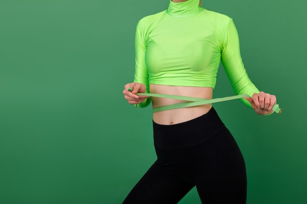 The girl holds a centimeter at the waist. sporting a healthy body.