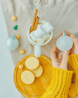 Girl holds christmas ball in her hand cup of cocoa with marshmallows and cinnamon cookies on a tray ...