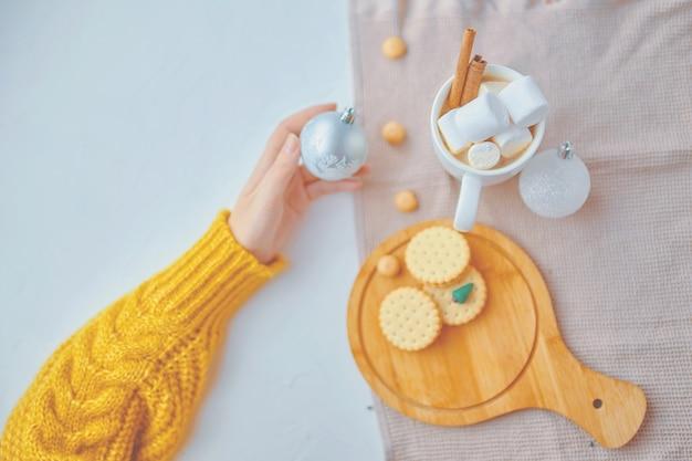 女の子は、トレイにマシュマロとシナモンクッキーを入れたココアのハンドカップにクリスマスボールを持っています...