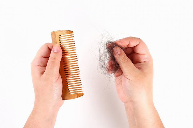 The girl holds a comb and lost hair