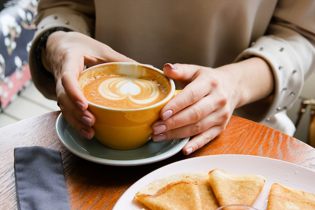 The girl holds a cup of coffee on a wooden table in the cafe.
