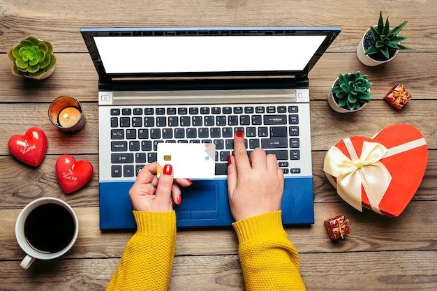 Девушка держит дебетовую карту, выбирает подарки, делает покупки, ноутбук, кофейную чашку, два сердца, сумку на деревянном столе