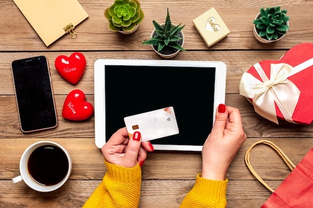 Girl holds debit card, chooses gifts, makes purchase, tablet, coffee cup, two hearts