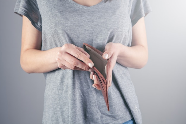 Girl holds an empty wallet in his hands.
