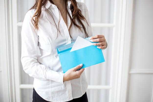 Девушка держит конверт, конверт с письмом или поручением, задание