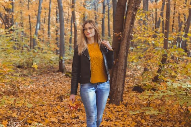 少女は落ち葉を持って秋の公園を散歩します。季節のコンセプト。