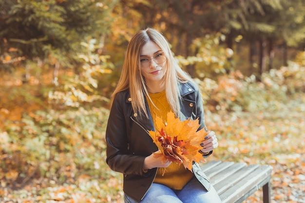 女の子は秋の公園で落ち葉を保持します。季節のコンセプト。