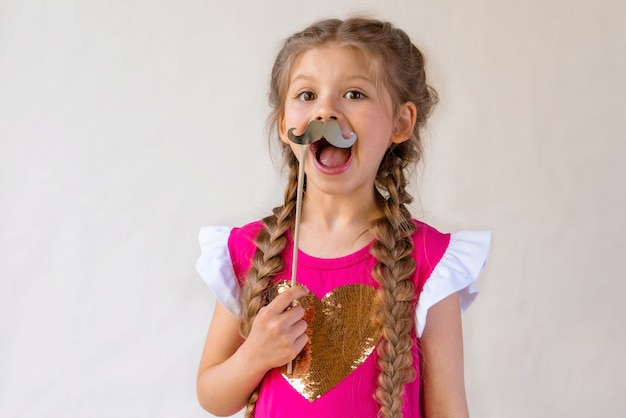 The girl holds a fancy moustache.