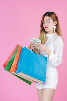 The girl holds a fashion shopping bag and holds a dollar card