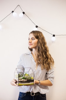 A girl holds a florariumov , glass shape with succulents, stones and sand, decorated with christmas ribbons. christmas gifts for home and office