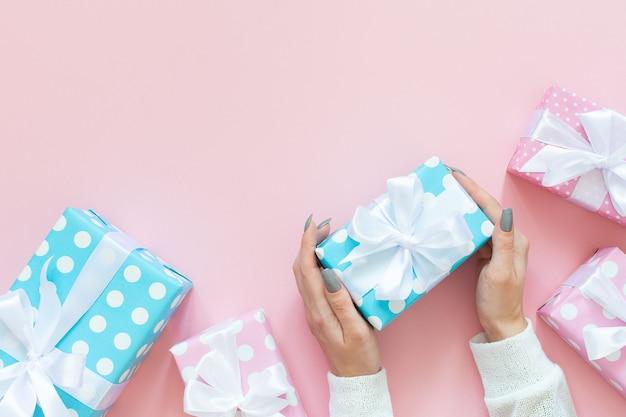 소녀는 흰색 리본이 달린 물방울 무늬의 선물 상자, 분홍색 및 파란색 선물 상자를 보유하고 있습니다.