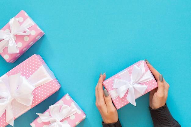 소녀는 흰색 리본과 활이있는 물방울 무늬의 선물 상자, 분홍색 선물 상자를 보유하고 있습니다.