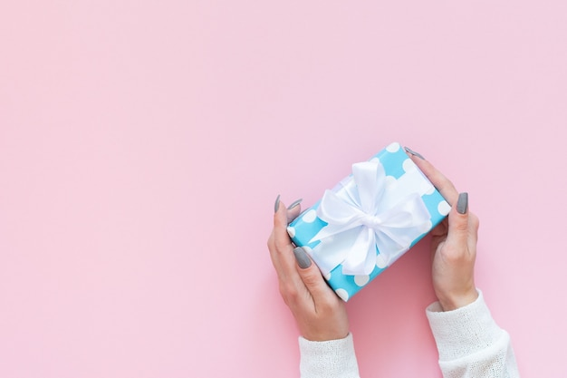 Girl holds gift box in polka dots with white ribbon and bow on a pink background
