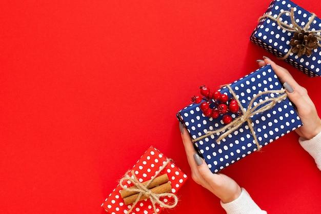 女の子は、クリスマス ツリーの円錐形の水玉模様のギフト ボックス、赤と青のギフト ボックスを保持し、緑の背景にドングリとシナモンを持つサンザシの小枝、フラット レイアウト、トップ ビュー