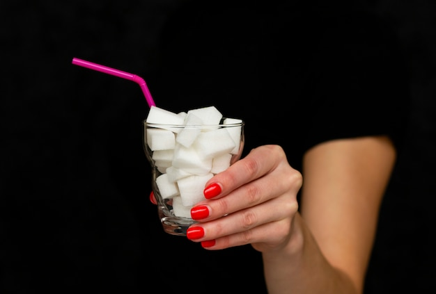 Girl holds a glass filled with cubes of white sugar,