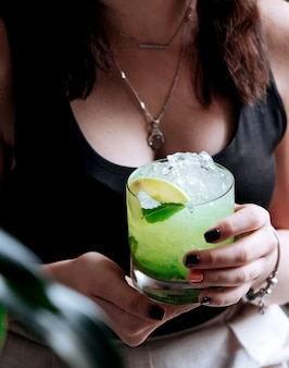 Girl holds a glass of mojito with lemon and mint