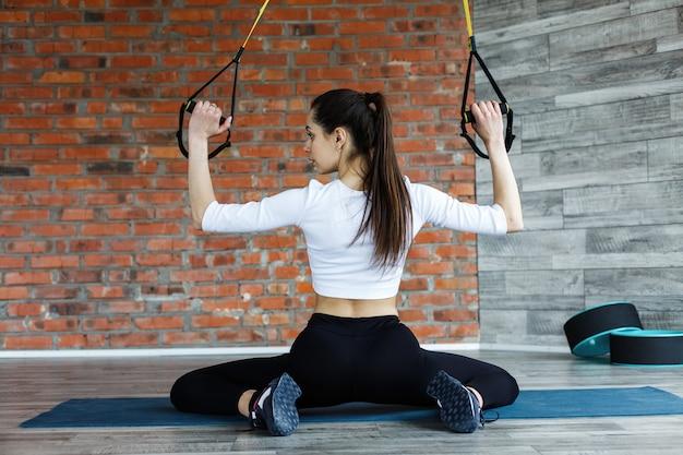 그녀는 체육관에서 운동을하는 동안 여자 체조 링을 보유