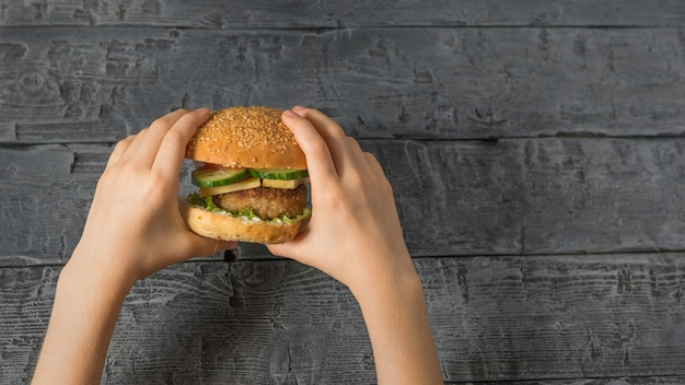 Girl holds a hamburger made with her own hands over a wooden table.