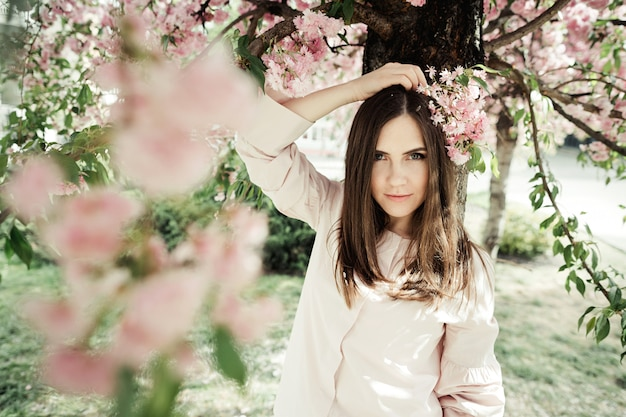 Girl holds hand behind her head with sakura branch and she stands near a sakura tree