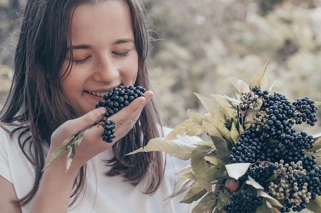 Girl holds in hands clusters fruit black elderberry in garden