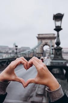 女の子はハートの形で手を保持しています。ブダペストを旅します。ブダペストの石造りの橋。