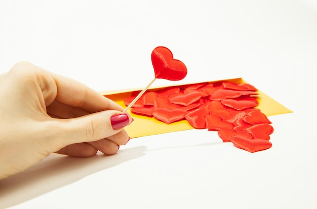 A girl holds a heart in her hand, next to a gold envelope and a lot of hearts, a situation of love in the distance