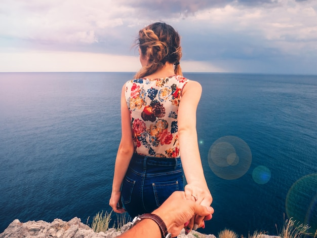Girl holds her boyfriend hand against the sea on a cliff on a summer day