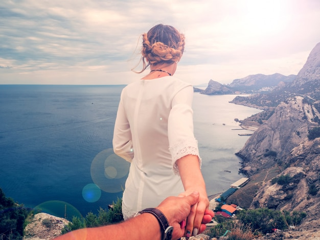 Girl holds her boyfriend's hand against the sea on a cliff on a summer day