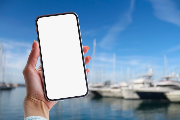 Girl holds in her hand a smartphone with white screen against the backdrop of the sea and yachts.