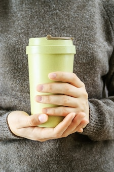 Girl holds in her hands  bamboo cup zero waste concept take away coffee i