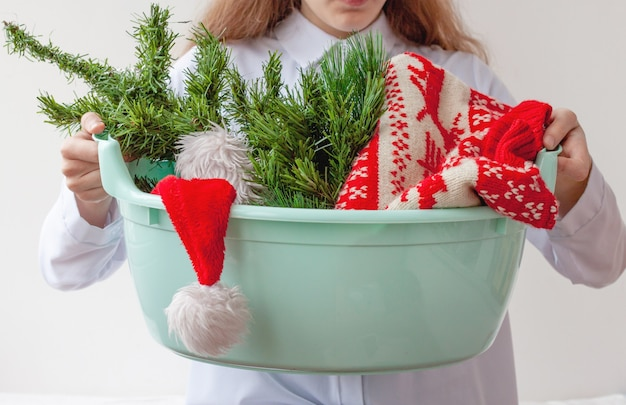 The girl holds in her hands a basin in which there is a small christmas tree a christmas sweater and...