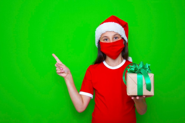 Girl holds in her hands gift for christmas holiday points finger in of place for advertising ads