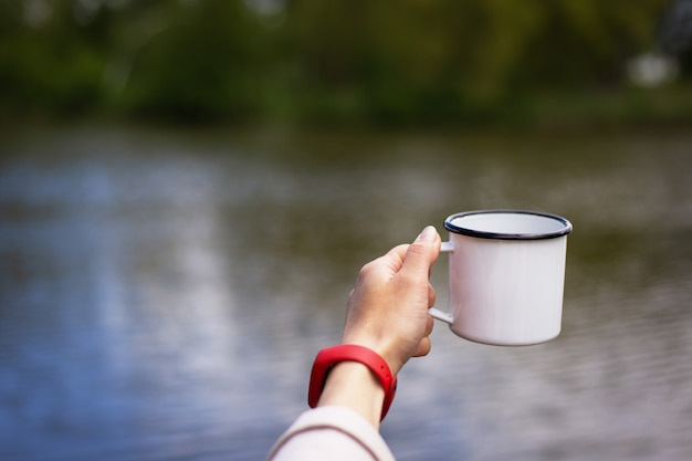 Girl holds in her hands a metal cup of coffee near the lake.