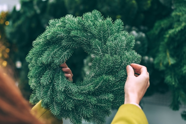 The girl holds in her hands a new year, christmas wreath, decorations for the home