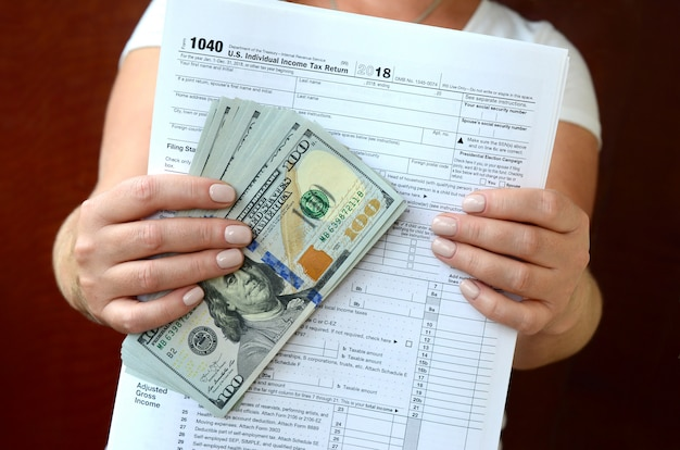 The girl holds in her hands the tax form and a large number of dollar bills