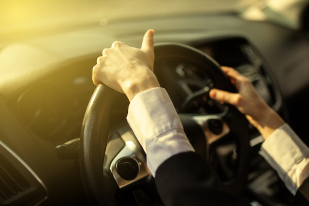 The girl holds her hands behind the wheel of the car