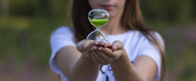 A girl holds an hourglass in her hands