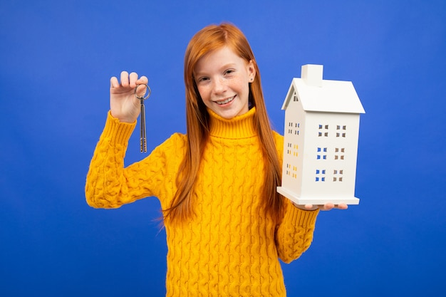 Girl holds a house model and door keys in hand on blue. the property